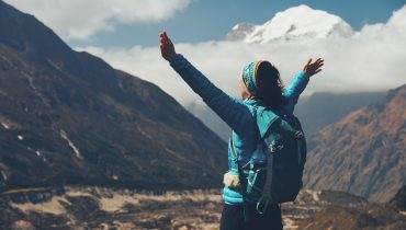 Standing young woman with backpack and raised up arms on the hill and looking on mountains. Landscape with happy girl, mountains, blue sky with clouds in autumn in Nepal. Travel. Trekking. Vintage